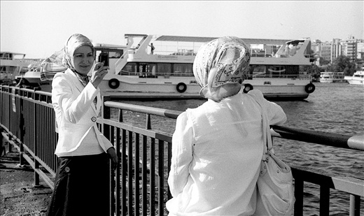 This picture was taken near one of the iskelasi (harbor) on the Bosphorus. It seemed that the women had just finished their office and were just having a moment of relief before heading for their respective homes. The fun of the picture is that the phone clicking the picture of the other women could even have been a mirror. The women were equally beautiful and clad in exactly the same way.