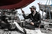 a man painting a boat in ezbet al-burg : by ships, Views[378]