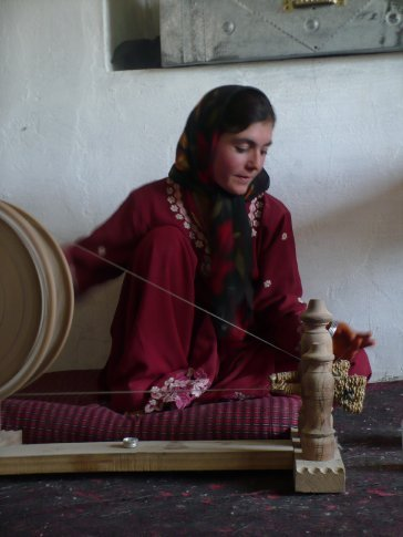 Young woman spinning goat's hair into thread in a cashmere processing workshop