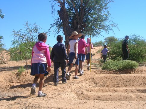 On their way to an impromptu lesson from Patrick, one of the community members driving the garden initiative