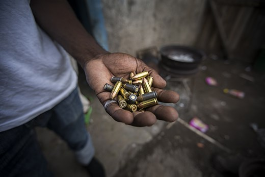 A gang member in Kingston, Jamaica holds a handful of bullets in his backyard.