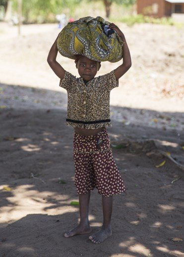 Passed on from ancient traditions, women including this young girl still carry loads on their heads where there is no less expensive, or more efficient, way of transporting things. Sometimes, women and girls carry up to 70% of their body weight on their heads. Men and boys are not seen doing this generally.