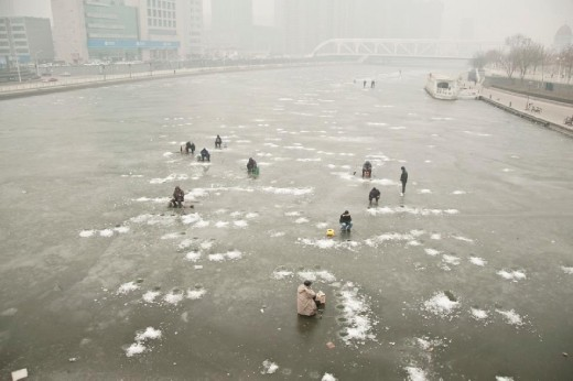 Fishing on the Haihe river  海河大桥.  During the winter time Tianjin River it became a long piece of ice. Tianjin people like to fish a lot, and the ice doesn't stop them