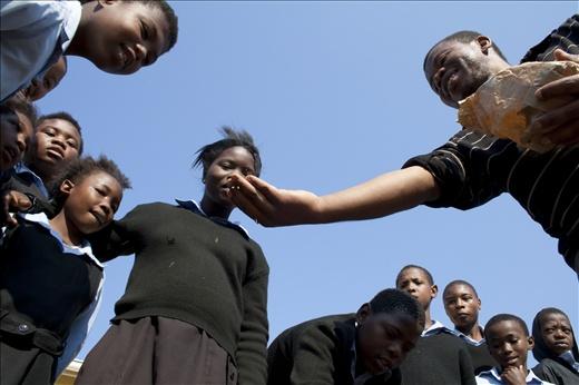 Xolela Mataleka of Umthathi  displays a handful of seeds to the pupils of Emanzi