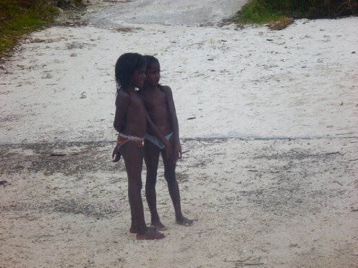 Two young islander girls watch as crowds of tourists descend upon their normally quiet island of Lifou. Tourists are the biggest source of income for islanders and young girls often braid hair and sell bracelets on the beach for coins.