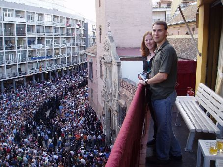 Shannon and Rob on the balcony with a procession going by