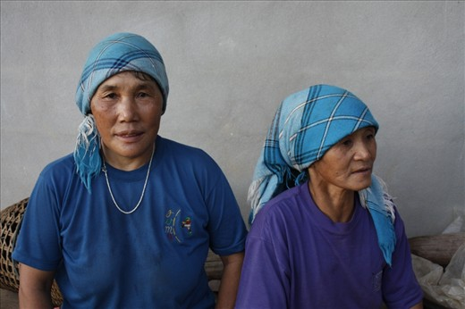 Two Akha women take a moment to rest between their six-hour days in the coffee fields and their numerous domestic responsibilities. Females play a large role in Akha society and culture.