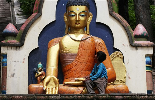 A small boy rests in the lap of a large Buddha statue at the base of Swayambhunath.