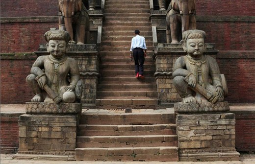 A solitary man ascends the stairs of a temple Patan Durbar Square, amidst crowds of tourists and merchants.