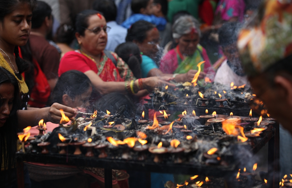 Women light candles during Janai Purnima celebrations, a festival in which women pray for their brothers' and husbands' well-being.