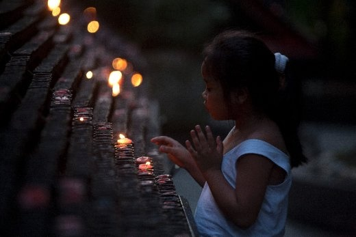 People also visit the church to light candles as offerings. In this image a little girl pauses her prayers, to attend to her candle blown by the wind. The number of candles lit by a person usually has a meaning. Pilgrims visiting the church on their birthdays, for example, light the same amount of candles equivalent to their age.