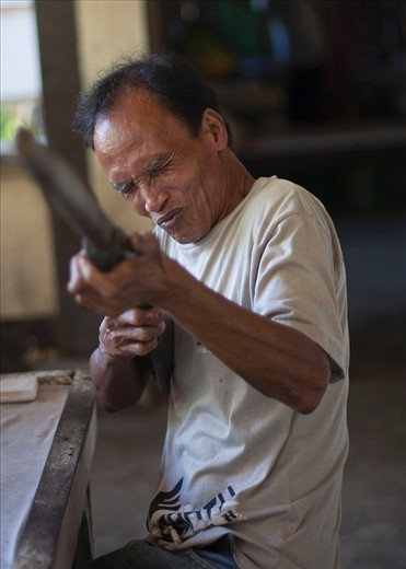 Most lepers in town still feel ashamed about their illness, this man seems to have accepted his situation, as he asks me to take a photograph with his wooden rifle.