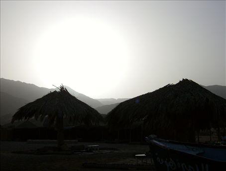 Hut silouhettes in the hazy sunlight.