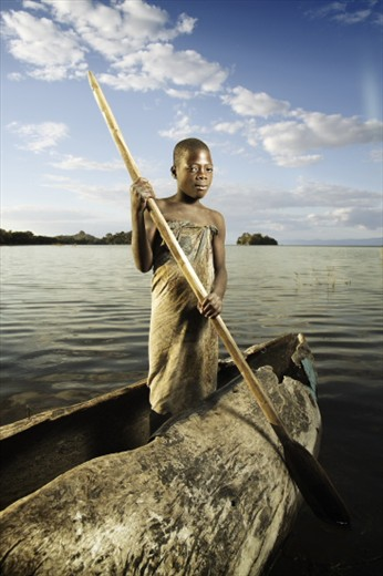 A young Malawian girl posing in a dugout canoe used for fishing.