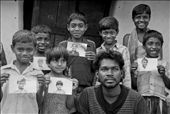A bunch of kids along with an elder guy is all smiles, as they pose with their photographs. I had done a small Help-Portrait session with these kids on my visit to Huchukpara, whereby I gave them a print of their portraits. None of them ever had a printed photograph of themselves before and this simple gesture lit up their priceless smiles!  Notice Sujoy's cheeky smile as he flashes his trademark unbuttoned pose in the photo.: by sudhyasheel, Views[397]