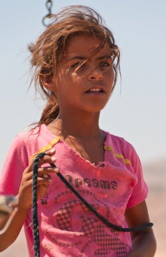 A local girl, holding a rope from a camel's neck, deep in her own thoughts looking far away.