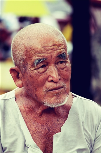An elderly man resting after a long cycle.