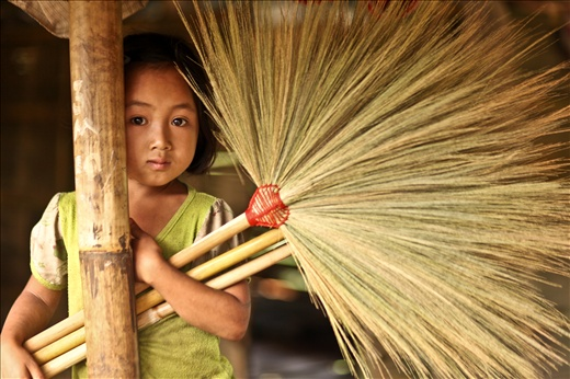Girl with a broom she made to sell in batches in the market