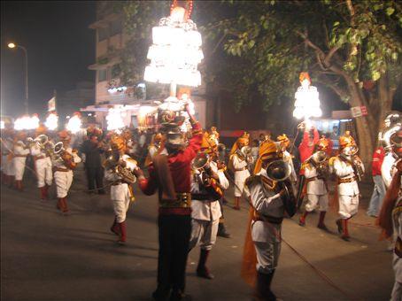 Processione con uomini-lampadario (e accluso