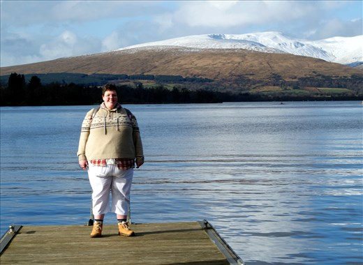 A photo of me, in warm walking gear (sweater, backpack [cropped] pants, walking boots), with Ben Lomond and Loch Lomond in the background.