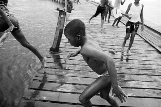 Children are everywhere. Many are sent to school during the day, others do not attend school and spend their time playing and swimming at the dock. On the warmest of days, the dock is slick with water as youngsters take turns launching themselves into the water below.