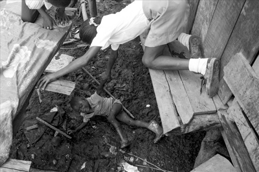 A large portion of the refugees in San Lorenzo live near the mangroves in stilt houses. As the tides rise, the floor beneath the houses are cleaned of debris and waste. The wooden boards that lead to and between the houses test ones balance, especially after heavy rain. Pictured here, a young boy is helped up by his siblings after falling from the house where he lives.