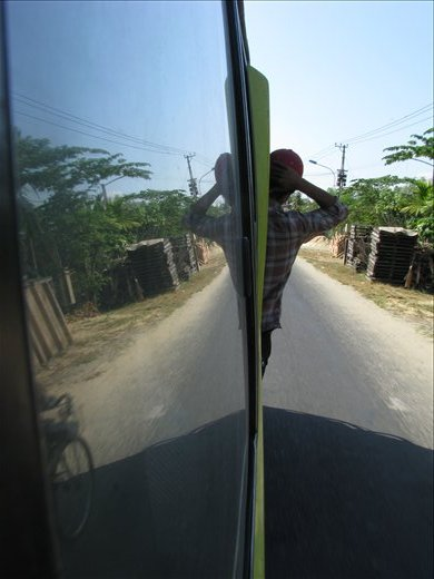 The local bus heading out of Hoi An - the assistant with his hawk eyes preying for more passengers