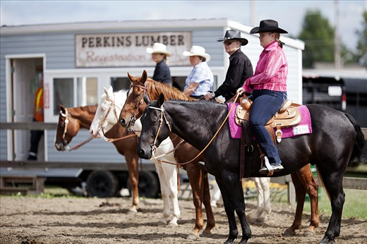 Four riders wait for their turns in an equestrian competition at the 2012 Richmond Fair, an annual festival that celebrates agriculture in the greater Ottawa community.