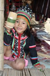 Young child in tradtional dress sitting on stall, suddenly saw us approach and picked up a bamboo container for sale, who could resist that happy smiling face.: by thailand, Views[142]