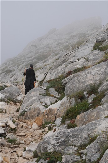 Walking down from the top of the mountain alone, between the mist and the wild rocks.