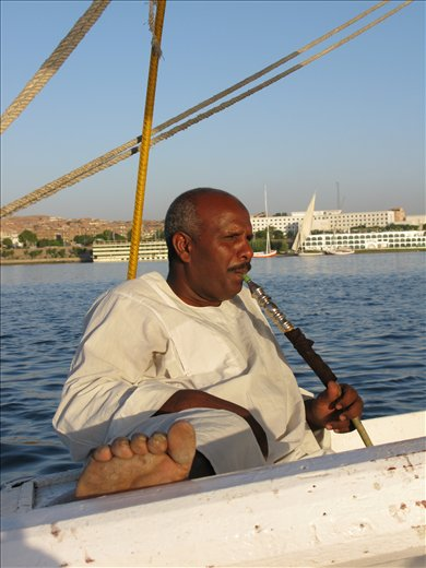 Auto-Pilot  A well seasoned faluca captain can afford to kick off his sandals and take a quick smoke break at the end of a long day sailing the Nile in Aswan.