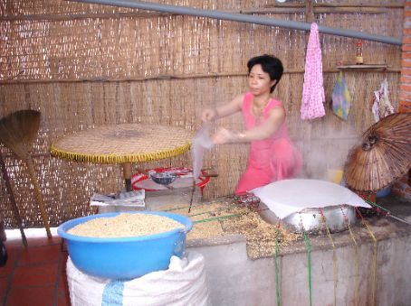 Woman making sheets of rice paper, later dried out in the sun.