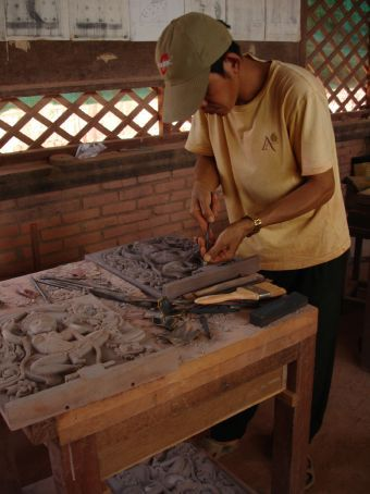 A man working on stone carvings at the artisan workshop.
