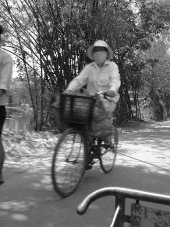A passing local on her bicycle within the Citadel in Hue
