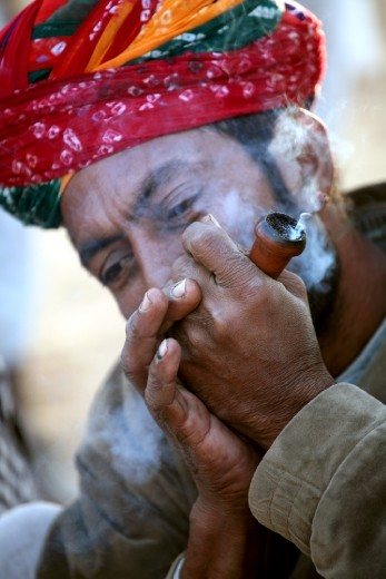 Break Time. A trader smoking a 'Chillum', Indian version of Pipe. Smoking marijuana is a common practice among traders and early mornings are not a deterrent for the enthusiasts.