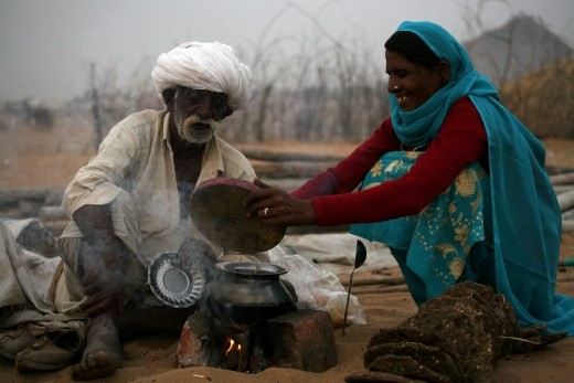 A Trader with his wife cooking dinner in the open field. In the evening you can see all over the trading field make shift 'Choolah' (cooking stove). Some traders come with their wives and few come with their friends but most of them cook their own food.