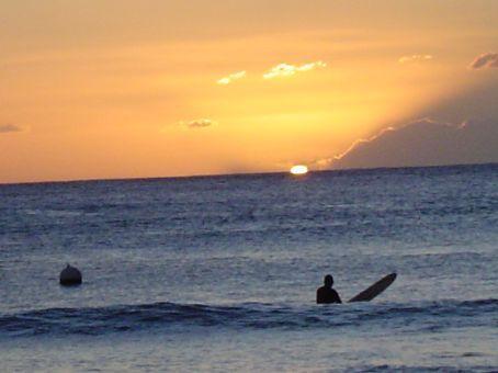 Surfer vor der untergehenden Sonne.