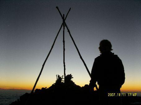Meine Umrisse vor dem Gipfelkreuz nach Sonnenuntergang.