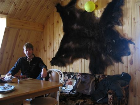 Tim relaxing with a bear behind.