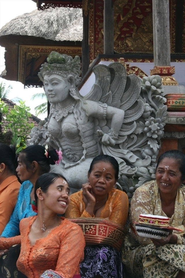 Woman's temple garb, in Balinese Hinduism is typically a bra under a transparent lace jacket, sarong and waist scarf. After temple is a social time.
