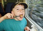 Declan making use of the Swiss Army knife between Alpnachstad and Interlaken - munching on his Bratwurst.: by tingays-in-europe, Views[1219]