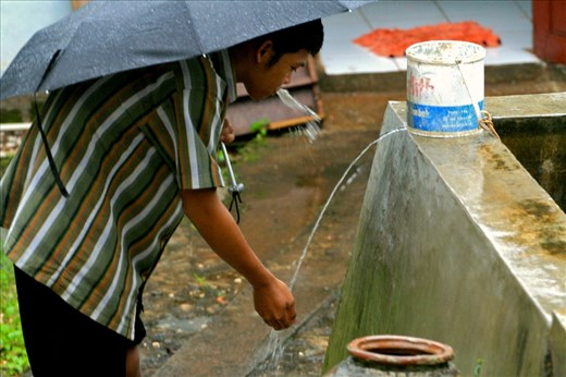 "Imsak, 27 year old, a young villager from Semanu, Gunungkidul, took a ""wudhu"" or an Islamic ritual before praying. He used the water from a reservoir tub held rainwater during the wet season."