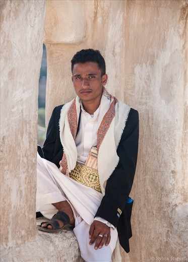 A Yemeni sitting on top of Dar al Hajar, the Imam's Rock Palace, outside of Sana'a. He is wearing the Jambiya, a traditional dagger worn by men as an accessory. The material and design of the handle tells the status of the one wearing it.