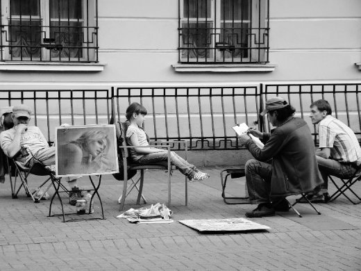 Artists sitting along the street doing portraits