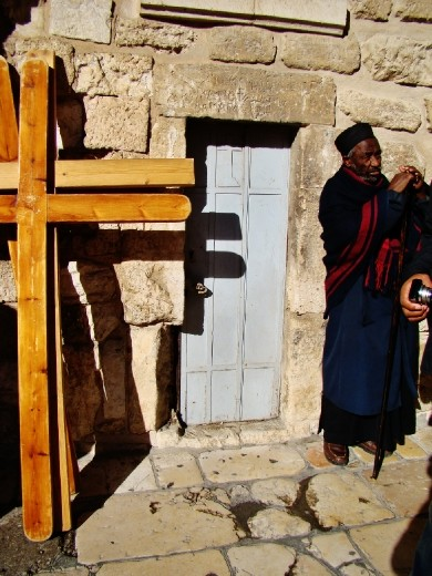 A priest standing in front of his small church
