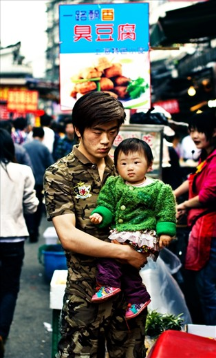 In a country that is developing very fast, family traditions are still strong. Here is a father with his child at Shanghai's Old City Market, both characters look thoughtful and in some way worried.
