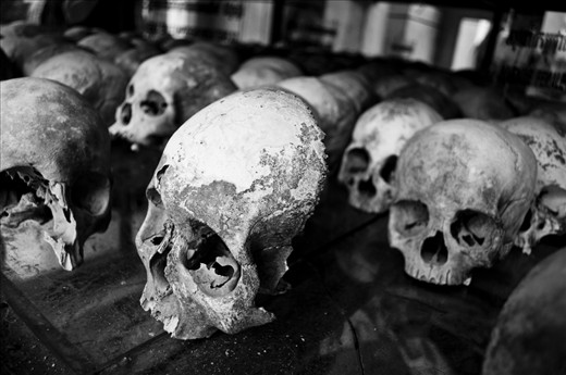 -The Innocent- This image was taken at the Choeung Ek Killing Field site. An orchard and Chinese graveyard before the Khmer Rouge regime in the `70s turned it into a killing field, it houses a Buddhist stupa which displays more than 5,000 human skulls that have been unearthed. An estimated 17,000 people were brutally executed at the Choeung Ek killing field site alone, including women, children and even babies. As you walk through the fields you can still see human bones coming up through the dirt.