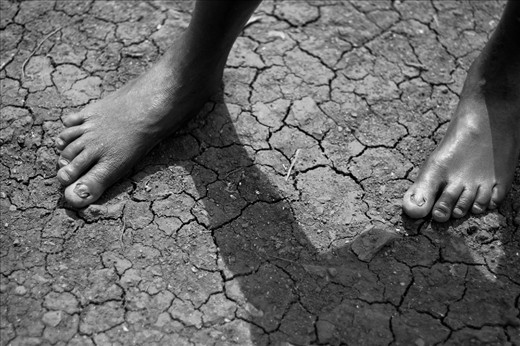 After this child has walked all morning to gather fresh water his feet almost blend into the backdrop of the cracked earth.