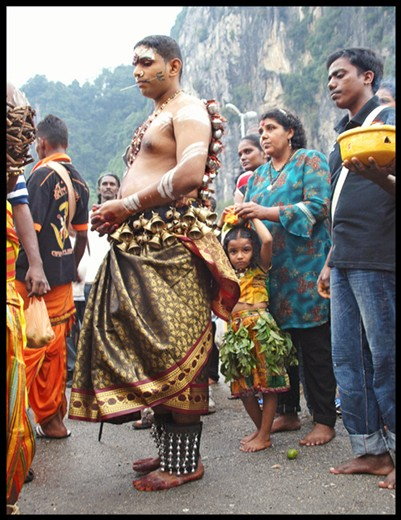 A young girl watches the participants at the annual Thaipusam festival in Malaysia.