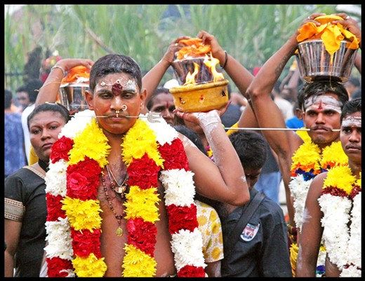 Colorful participants at the annual Thaipusam festival wearing garlands and carrying flaming pots.